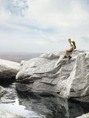 Traveler girl sitting on a rock — Foto Stock