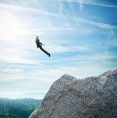 Man in suit flying over mountains — Stock Photo