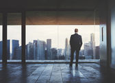 Businessman looking at city through window — Stock Photo