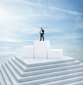 Businessman standing on highest cube — Stock Photo