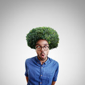 Young cross-eyed man with green bush — Stock Photo