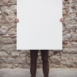 Young man holding blank poster — Stock Photo #41457369