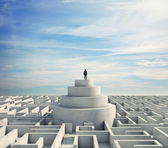 Man standing on podium in the middle of a maze — 图库照片