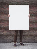 Man holding blank poster — Stock Photo