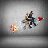 Businessman and young woman flying with rocket — Stock Photo