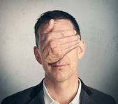 Portrait of a man with hand closing his eyes — Stock Photo