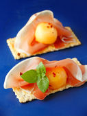 Finger food with melon, prosciutto and crackers — Stock Photo