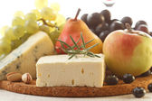 Various types of cheese and fruits — Stock Photo