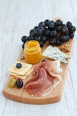 Appetizer with ham, cheese and fruits — Stock Photo