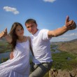Couple  showing trumbs up in mountains — Stock Photo