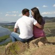 Couple sitting on a rock in mountains — Stok fotoğraf