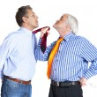 Businessman pulling a tie to younger man — Stock Photo
