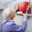 Stock Photo: Minstalls fire extinguisher