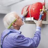 Człowiek instaluje gaśnica — Zdjęcie stockowe