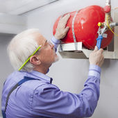 Man installs fire extinguisher — Stock Photo