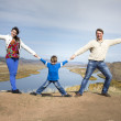 Happy family holding hands together on the mountain — Stock Photo #32586375