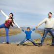 Happy family holding hands together on the mountain — Stock Photo #32586383