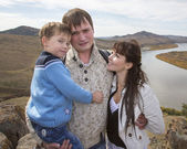 Happy family on the mountain with lake — Stock Photo