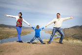 Happy family holding hands together on the mountain — Stock Photo