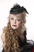 Woman with curly hair in pretty hat — Stock Photo
