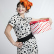 Happy girl holding gift box with red polka dots — Stock Photo #39167401