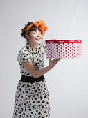 Happy girl opening gift box with red polka dots — Stock Photo