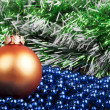 Orange Christmas ball and blue beads on a background of green ga — Stock Photo