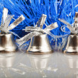 Three silver bells on the background of blue garland — Stock Photo