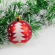 Red Christmas ball with painted Christmas tree and green garland — Stock Photo