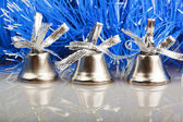 Three silver bells on the background of blue garland — Stockfoto