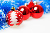 Three red Christmas balls on a background of blue garland — Stock Photo