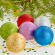 Several multicolored Christmas balls under the tree — Stock Photo