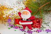 Santa claus with a drum and a gift under the tree — Stock Photo