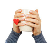 Female hands holding a cup with paper heart — Stock Photo