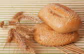 Two buns with wheat spikelets — Stock Photo