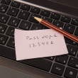 Sticky note with password and pencil on black laptop — Stock Photo #50675383