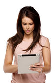 Brunette woman using a computer tablet — Stock Photo