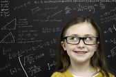 Smart young girl stood infront of a blackboard — Stock Photo