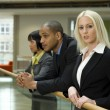 Blonde business woman and two co-workers — Stock Photo