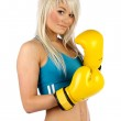 Young blonde woman with yellow boxing gloves on — Stock Photo