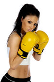 Young brunette woman with yellow boxing gloves on — Stock Photo