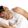 Man laid in white bed next to a sleeping woman — Stock Photo