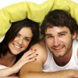 Beautiful couple in bed under a green duvet — Stock Photo