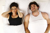 Man snoring keeping woman awake in bed — Stock Photo