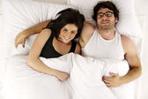 Man and woman laid in white bed looking up at the camera smiling — Stock Photo