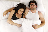 Man and woman laid in white bed asleep cuddling — Stock Photo