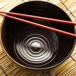 Red chopsticks and black bowl — Stock Photo