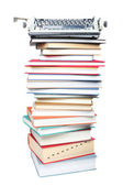 Stack of books and typewriter on white background — Stock Photo