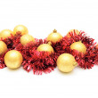 Christmas card.Yellow spheres and red tinsel. — Stock Photo