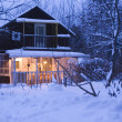 Wooden house in dark winter forest — Stock Photo